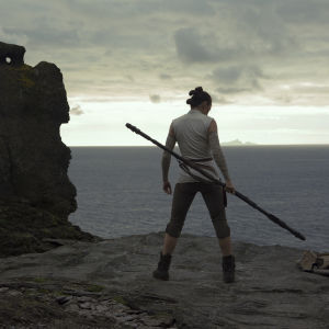 Rey (Daisy Ridley) tränar på en hög klippavsats vid havet.