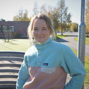 Blond kvinna i fleecejacka står på en fotbollsplan.
