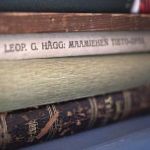 """Tre gamla böcker på hög, varav den översta är skriven av Leopold G. Hägg och heter """"Maamiehen tieto-opas""""."""