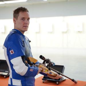 Niklas Hyvärinen står med ett gevär i händerna.