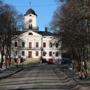 En byggnad i vitt och fotgängare som går på en trottoar.