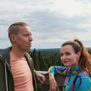 Mies ja nainen seisovat ja nojaavat kaiteeseen korkealla. Taustalla näkyy metsää, vaaroja ja pilvipoutaista taivasta.