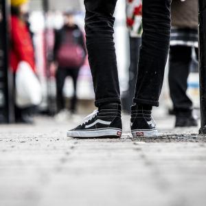 Nuori seisomassa bussipysäkillä