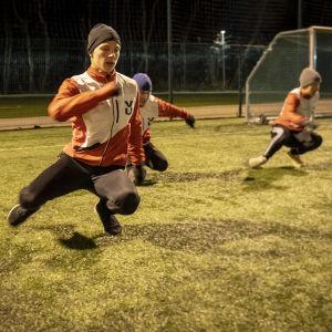 Nuoret yleisurheilijat harjoittelevat ulkosalla.