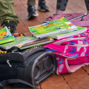 Kasa koulukirjoja koulureppujen päällä.