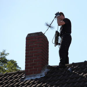 En sotare står vid en skorsten på ett hustak.
