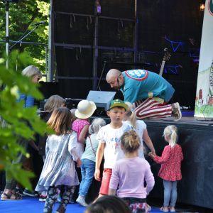 Apan Anders delar ut skivor till barn.