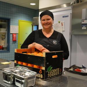 Kvinna med en låda apelsiner framför sig.