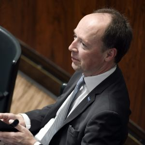 Sannfinländarnas ordförande Jussi Halla-aho sitter i plenisalen med telefonen i handen.