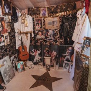 Pieni huone täynnä Elvis Presley-artistiin liittyvää tavaraa: kuvia, kitara, nukke, kaksi valkoista esiintymisasua. Lattiaan maalattu kullanvärisellä maalilla tähti sekä teksti Elvis Presley.