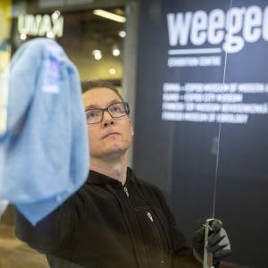 Käyttömestari Antti Schroderus puhdistaa suojapleksejä WeeGee-talossa.