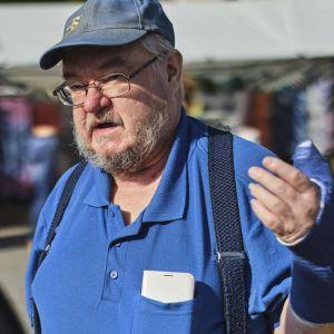 Sannfinländaren Pekka Kataja står på ett torg och pratar. Han håller ena armen uppe, den är täckt i gips.