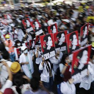 Porträtt på landets störtade civila ledare Aung San Suu Kyi förekommer på alla demonstrationer. Här på en av demonstrationerna i Rangoon idag, 25.2.