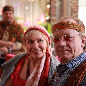Ainon kahvilan 60-luku bileissä Aino ja Ensio pukeutuneena hipeiksi. Aino katsoo Ensiota.