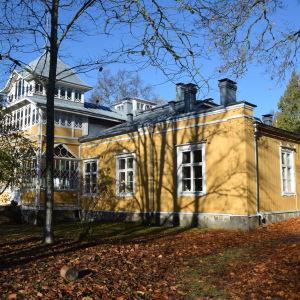 Ett gult gammalt hus skymtar bakom några träd. På markens ligger höstlöv.