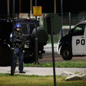 En tungt beväpnad polis står vid ett par polisbilar.