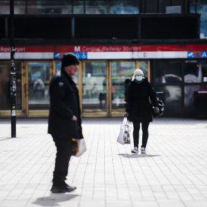 En man i förgrunden och en kvinna med munskydd i bakgrunden som går bort från en metrostation i Helsingfors.