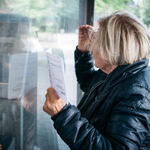 Eläkeikäinen nainen pankin ulkupuolella lasku kädessä.