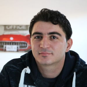 En syrisk ung man med mörkt hår. I bakgrunden skymtar en tavla med en röd amerikansk bil som motiv.