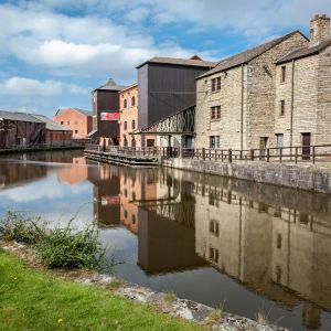 Industriområdet Wigan Pier var ett centrum för den tillverkande industrin i staden. På bilden ser historiska industrianläggningar vid ett vattendrag.