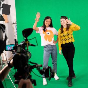 Kaksi naista heiluttamassa kameralle studiossa vihreän taustan edessä.