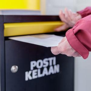 Naisen kädet laittavat kirjeen Kelan postilaatikkoon. Postilaatikossa teksti: Posti Kelaan.