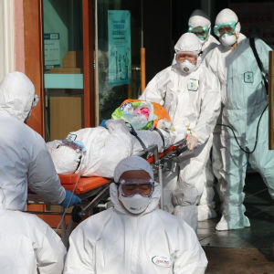 Människor iklädda masker och vita overaller flyttar patient på bår.