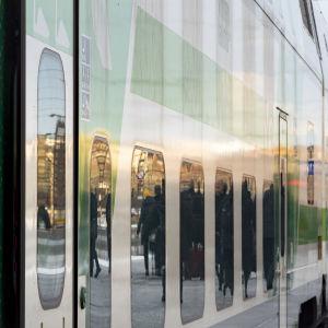 Fjärrtåg vid en perrong, närbild av vagnens fönster som reflekterar passagerare.