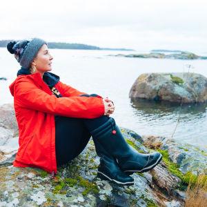 Kvinna i röd jacka sitter på en klippa och ser ut över havet.