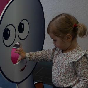 BUU-dagen i Hfors 2019. En liten flicka kastar en boll igenom en paff-buustämpel
