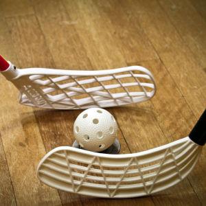 Närbild på två innebandyklubbor och en boll vid tekning