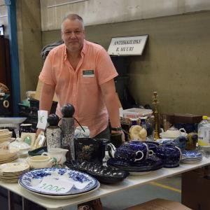 Antikhandlare Risto Muuri står bakom sitt försäljningsstånd.