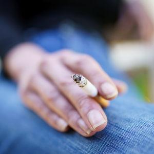 Naisen käsi, jossa sormien välissä palava savuke.