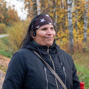 Paulina Hannusstår i en mörk jacka och ett pannband på en sluttande gångväg av asfalt. I bakgrunden syns olika lövträd i höstiga färger.