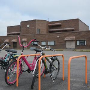 Cyklar vid ett cykelställ på en skolgård
