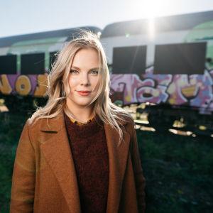 En kvinna i ljust hår står framför ett tåg