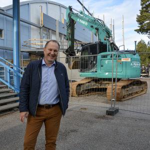 Tomas Kurtén, vd för Vasa Sport, står leendes intill ishallen i Vasa som renoveras. En grävmaskin syns i bakgrunden.