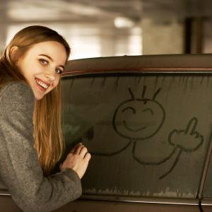 En kvinna ritar en glad gubbe på ett smutsigt bilfönster, men gubben visar mittfingret. Hon själv ler till kameran.