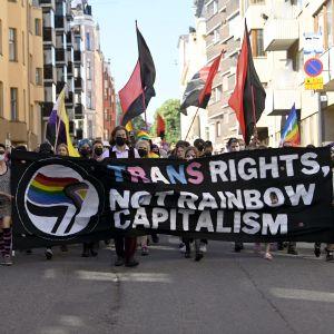 Pride paraden, personer går på gatan.