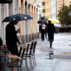 Människor med paraply i ett regnigt Berghäll.