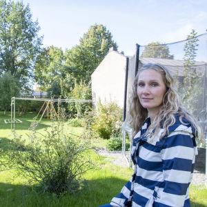 Lotta Eskelinen står på sin bakgård. I bakgrunden ser man taket av ett radhus.