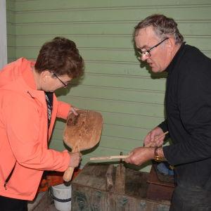 Kvinna och man ser på gamla träföremål.