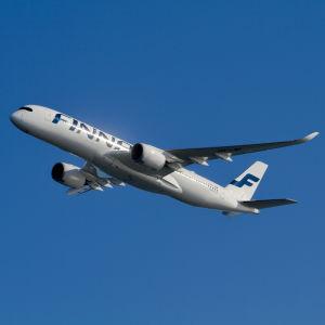 Finnairs Airbus A350 flygande med blå himmel i bakgrunden.