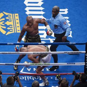 Floyd Mayweather håller på att slå ner Conor McGregor.