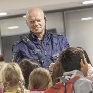 En polis i uniform tittar mot kameran. Runt omkring honom massor med barn.