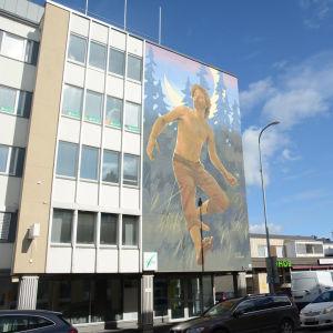 Rakennuksen seinään maalattu muraali, jossa mies juoksee metsässä kuutamossa.