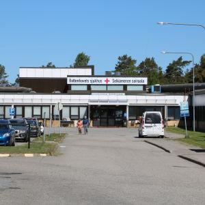 En sjukhusbyggnad i bakgrunden. Fram i bilden en parkeringsplats med flertal bilar.