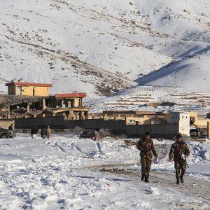 Afghanska säkerhetsstyrkor går nära militärbasen, där en bilbomb har exploderat.