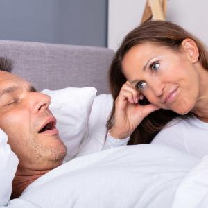 Kvinna tittar utamattat på sovande man som har öppen mun