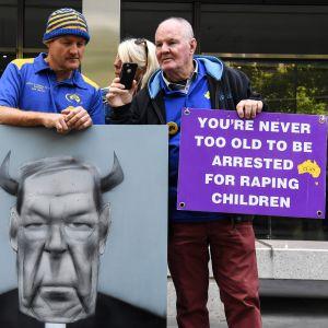"""Demonstranter utanför domstolen i Melbourne med ett plakat där det står: """"Du är aldrig för gammal för att gripas för våldtäkt av barn""""."""